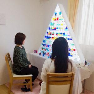 三角形のおーラソーマの棚からボトルを選んでいるところ